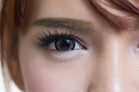 Close-up shot of asian woman eye with contact lens gray colour
