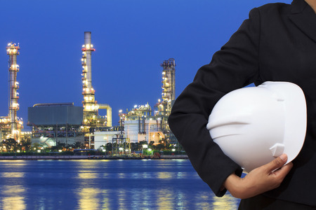 Engineer holding yellow helmet for workers security on beautiful oil refinery background