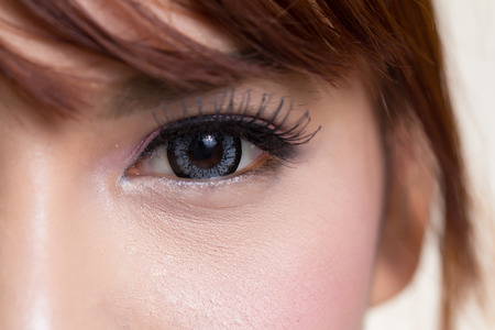 black eyes: Close-up shot of asian woman eye with contact lens gray colour