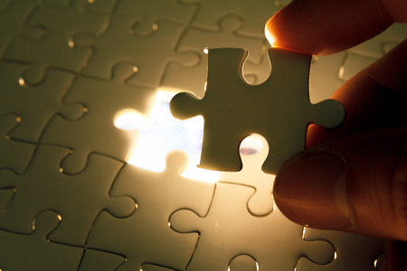 final piece of puzzle: Hand insert missing jigsaw puzzle piece with light glow, business concept for completing the final puzzle piece