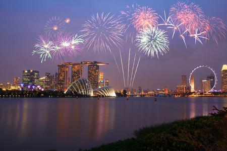 dia y la noche: Fuegos artificiales sobre Marina Bay en Singapur en fuegos artificiales del día nacional de celebración Editorial