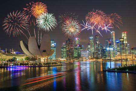 dia y noche: Fuegos artificiales sobre Marina Bay en Singapur en fuegos artificiales del día nacional de celebración Editorial
