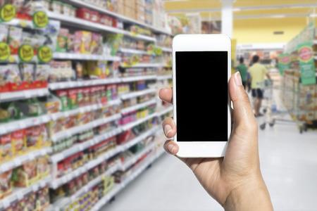 여성의 손을 슈퍼마켓에 모바일 스마트 전화를 들고 배경, 비즈니스 개념을 흐리게 스톡 콘텐츠 - 45950432