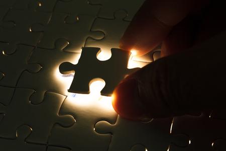 piezas de rompecabezas: Inserci�n de la mano el pedazo que falta de rompecabezas con resplandor de luz, concepto de negocio para completar la pieza final del rompecabezas