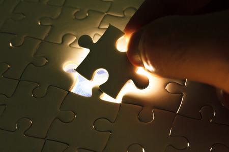 Insert de main manque de pièce de puzzle avec une lueur de lumière, concept d'entreprise pour remplir la pièce de puzzle final