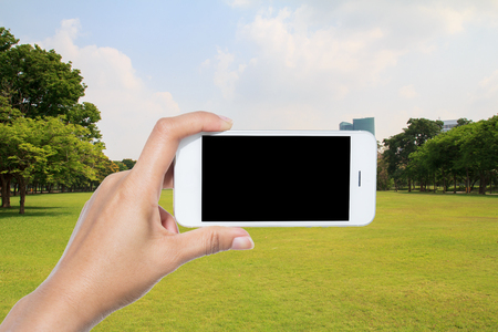 Hand holding smart phone on City park under blue sky with building background