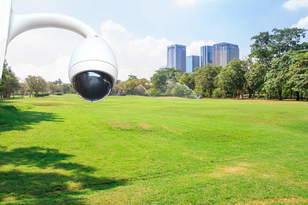 security camera in City park under blue sky with building background Stock Photo