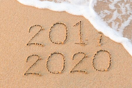 New Year 2020 is coming concept. Happy New Year 2020 replace 2019 concept on the sea beach 스톡 콘텐츠