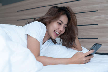 Young asian women lying in bed texting and checking social apps in smartphone on bed before after she sleeping at night. Mobile addict concept.