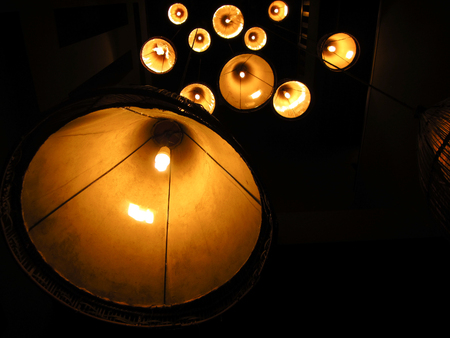 Multiple warm lamps with light yellow spots at night.