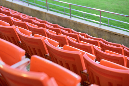 Row of orange seat for watch some sport or football.