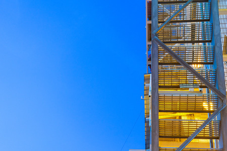 sidewall: fire escape ladder upper view on offshore platform with lighting in evening.