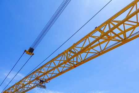 maneuverable: Crane boom structure and metal sling on blue sky background