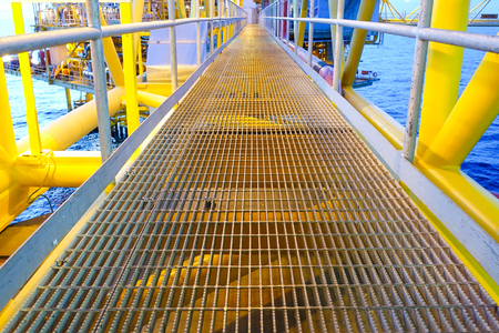 sidewall: Bridge and handrail with grating on offshore platform with lighting in evening.
