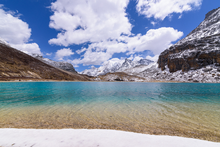 jokul: Milk lake on top,green and blue with snow beach on the top of snow mountains with blue sky and clouds background at Yading Nature Reserve, China.