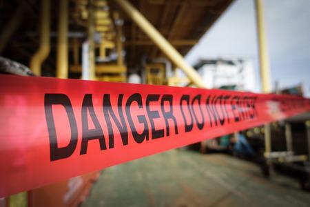 사람들이 들어오는 것을 막기 위해 공장 산업에서 빨간색 위험 테이프 바리케이드의 어두운 색조.