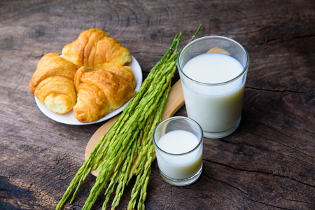 Croissant on dish with rice milk and ear of rice  on old wooden table for breakfast background. Stock Photo