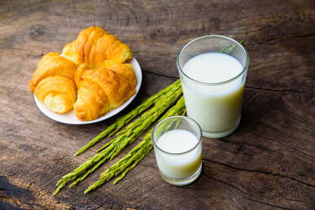 sudio: Croissant on dish with rice milk and ear of rice  on old wooden table for breakfast background. Stock Photo