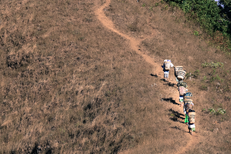 Abstract Groups of Porter or Sherpas while carrying the baggage of trekking up to the top of Doi Monjong the mountain in Chiangmai, Thailand, vintage tone for patient concept.