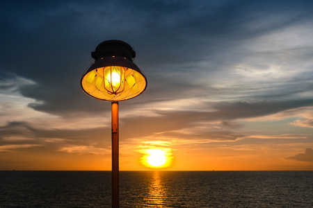 Lighting of warm lamp and lighting of sunset at sea with beautiful sky and clouds in the evening with twilight time on offshore platform. Stock Photo