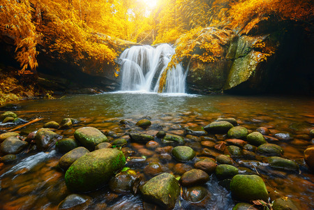 Landscape photo, Phu Soi Dao Waterfall with yellow leaves trees, beautiful waterfall in rainforest at Uttaradit province, Thailand
