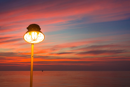 chandelier: Lighting of warm lamp or yellow HID lamp and lighting of sunset at sea with beautiful sky and clouds in the evening with twilight time and silhouette on offshore platform. Stock Photo