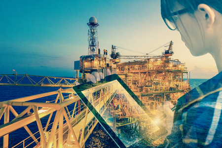 Double exposure of businesswoman in hipster shirt and wearing glasses working with tablet and oil and gas refinery industry plant in the night as Energy and Technology concept.