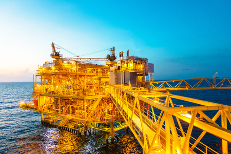esbjerg: Offshore construction platform for production oil and gas with bridge in evening time Stock Photo