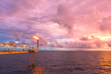 Gas flare is releasing and burning to the atmosphere at an offshore gas platform with clouds and sky in twilight time Stock Photo