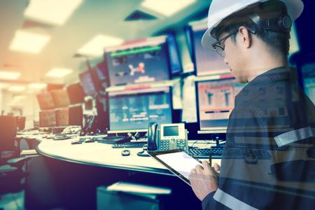 Dubbele blootstelling van ingenieur of technicus man in werkend shirt werken met tablet in controle kamer van olie- en gasplatform of plantenindustrie voor monitorproces, bedrijfs- en industrieconcept Stockfoto