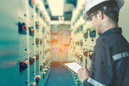 モニター プロセス、ビジネスおよび産業という概念の石油と天然ガス プラットフォームの産業工場のスイッチ ギア電気ルームでタブレットを使用