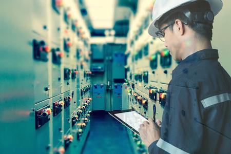 Dubbele blootstelling van ingenieur of technicus man aan het werk met tablet in elektrische schakellokaal kamer van olie- en gasplatform of industriële plant voor monitor proces, business en industrie concept