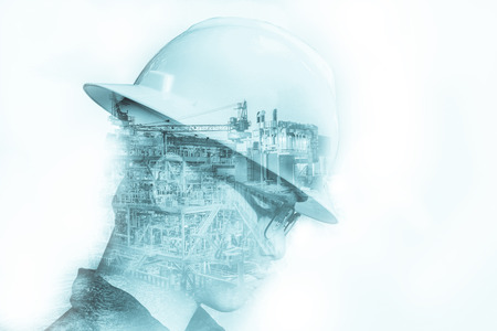 Double exposure of Engineer or Technician man with safety helmet operated platform or plant by using tablet with offshore oil and gas platform background for oil and gas business concept.