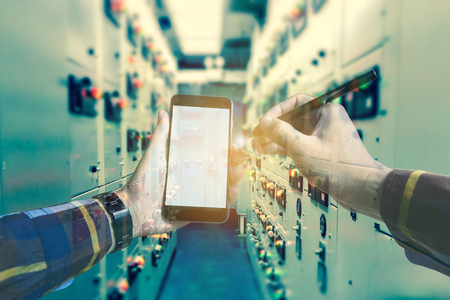 dispatcher: Double exposure of  hand working with smart phone in switch gearl room of oil and gas platform or plant industrial for monitor process, business and industry concept.