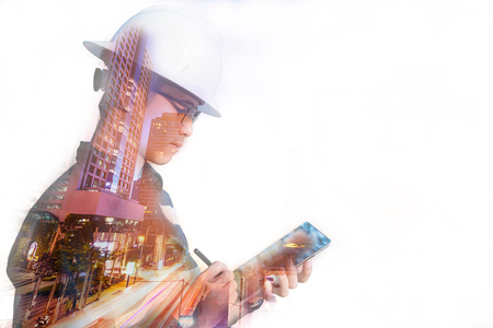 Double exposure of  Engineer or Architecture man in working shirt and safety helmet working with tablet in night building background , business and construction concept. Stock Photo