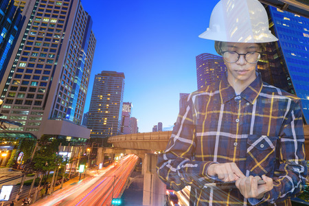Double exposure of  Engineer or Architecture women in working shirt and safety helmet working with tablet in night building background , business and construction concept.