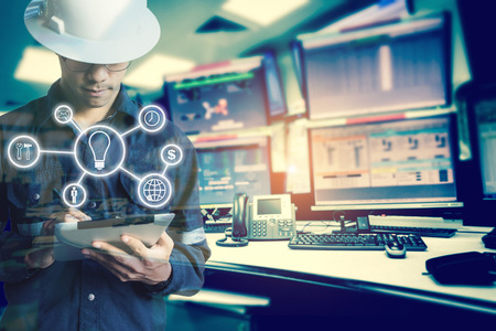 Double exposure of Engineer or Technician man with business industrial tool icons while using tablet with monitor of computers room  for oil and gas industrial business concept. Stok Fotoğraf - 84684846