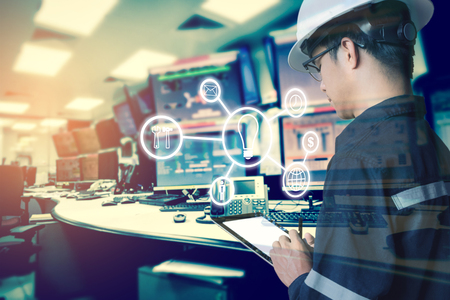 Double exposure of Engineer or Technician man with business industrial tool icons while using tablet with monitor of computers room  for oil and gas industrial business concept. 스톡 콘텐츠