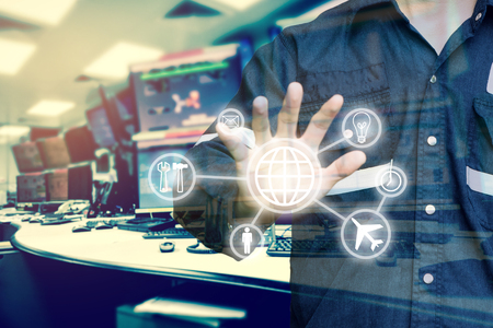 Double exposure of Engineer or Technician man with business industrial tool icons while using hand control monitor of computers room  for oil and gas industrial business concept.