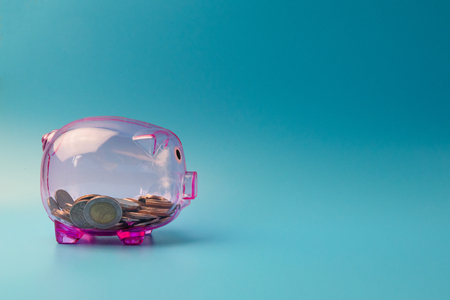 Clear Pink Piggy bank on blue background with coins for saving money concept. Stock Photo