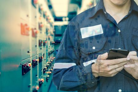 Doppelbelichtung des Ingenieur- oder Technikermannes, der intelligentes Telefon für die Steuerung elektrisch im elektrischen Raum des Schaltgangs der Öl- und Gasplattform oder der Anlage industriell für Überwachungsprozeß-, Geschäfts- und Industriekonzept verwendet. Standard-Bild - 88760455