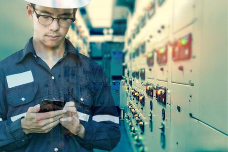 Double exposition de l'homme ingénieur ou technicien en utilisant un téléphone intelligent pour le contrôle électrique dans la salle électrique de l'appareillage électrique de la plate-forme pétrolière et gazière ou usine industrielle pour le concept de processus de contrôle, d'affaires et de l'industrie.
