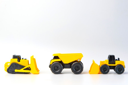 Under construction concept, with group of human toy and heavy duty machinery vehicle on white background with copy space for mocup your product.