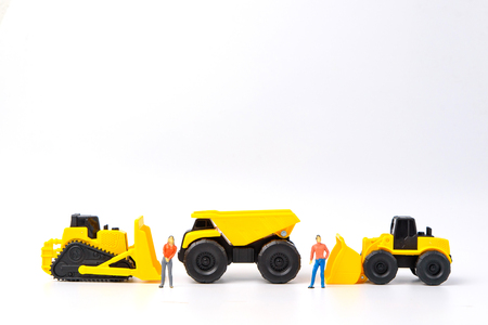 Under construction concept, with group of human toy and heavy duty machinery on white background with copy space for mocup your product.