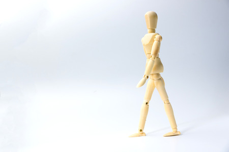 Wooden figure doll with walking action for business concept on white background.