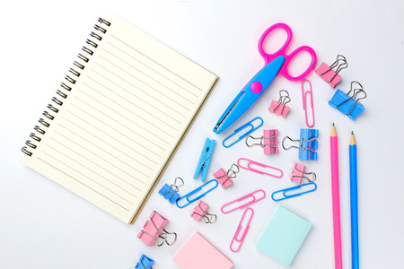 Stationary concept, Flat Lay top view Photo of Scissors, pencils, paper clips, sticky note,staple with blank note pad in pink and blue tone on white background with copy space. Stock Photo