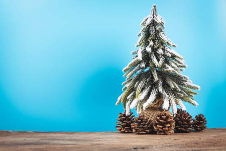 Christmas or New Year background with pine tree of Xmas decorations and fir branches, blank space for a greeting text on wooden board. Stock Photo