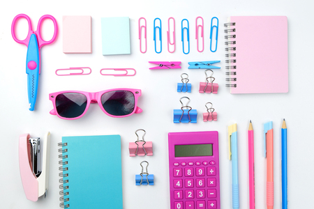 Stationary concept, Flat Lay top view Photo of Scissors, pencils, paper clips, sunglasses,sticky note,stapler and notepad with pink sun glasses in pastel tone on white background with copy space.