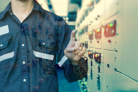 Double exposure of  Engineer or Technician man press his finger action in switch gear electrical room of oil and gas platform or plant industrial for monitor process, business and industry concept. Banque d'images