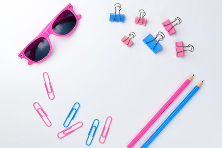 Stationary concept, Flat Lay top view Photo of Scissors, pencils, paper clips, sunglasses,sticky note,stapler and notepad in pink and blue tone on white background with copy space. Stock Photo